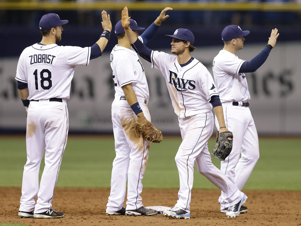 Photo - Tampa Bay Rays' Wil Myers, second from right, high fives teammates Evan Longoria, right, James Loney, second from left, and Ben Zobrist, left, after the team defeated the Toronto Blue Jays 9-2 during a baseball game Monday, March 31, 2014, in St. Petersburg, Fla. (AP Photo/Chris O'Meara)