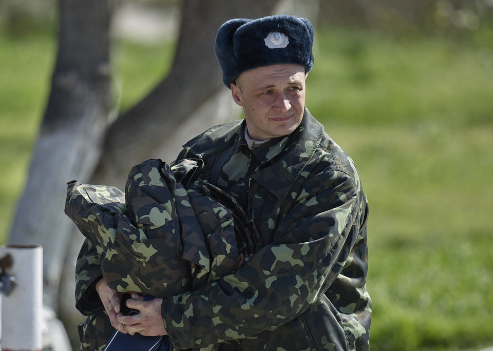 Photo - A Ukrainian airman carries belongings as he leaves the Belbek air base, outside Sevastopol, Crimea, Friday, March 21, 2014. The base commander Col. Yuliy Mamchur said he was asked by the Russian military to turn over the base but is unwilling to do so until he receives orders from the Ukrainian defense ministry.(AP Photo/Vadim Ghirda)