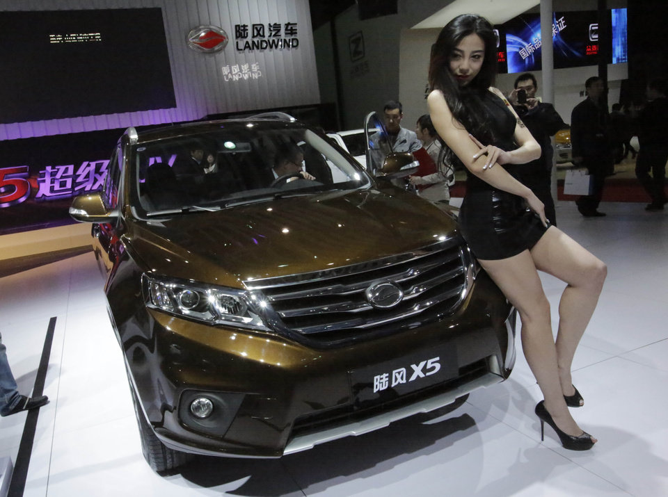 Photo - In this Saturday, April 20, 2013 photo, a model poses with the new Landwind X5 SUV at the Shanghai International Automobile Industry Exhibition (AUTO Shanghai) media day in Shanghai, China. SUV sales in China rose 20 percent last year to 2.5 million vehicles, more than double the 8 percent growth of the overall auto market, according to LMC Automotive. SUVs made up 18 percent of all vehicles sold. (AP Photo/Eugene Hoshiko)