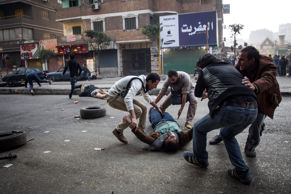 Photo - A mortally wounded supporter of Egypt's ousted Islamist president is evacuated as another wounded protester lies in the street during clashes with security forces in the Mohandiseen district of Cairo, Egypt, Saturday, Jan. 25, 2014. In large, state-backed rallies complete with dancing horses and traditional music, military supporters celebrated the anniversary of Egypt's 2011 uprising Saturday, calling for the army chief to run for president. At the same time, security forces cracked down on rival demonstrations by Islamist supporters of the ousted president — and by secular activists critical of both camps.(AP Photo/Eman Helal)