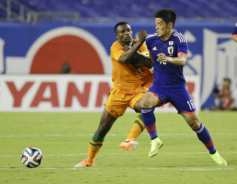 Photo - Zambia's Christopher Katongo, left, tries to stop Japan's Hotaru Yamaguchi (16) from getting to the ball during the second half of an international friendly soccer match in Tampa, Fla., Friday, June 6, 2014. Japan won 4-3. (AP Photo/John Raoux)