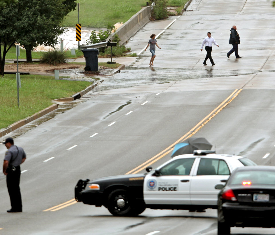 Photo - Police block Hefner road as local residents leave the area as water spills over the dam south of Hefner between Macarthur and Rockwell in Oklahoma City on Monday, June 14, 2010. Photo by John Clanton, The Oklahoman