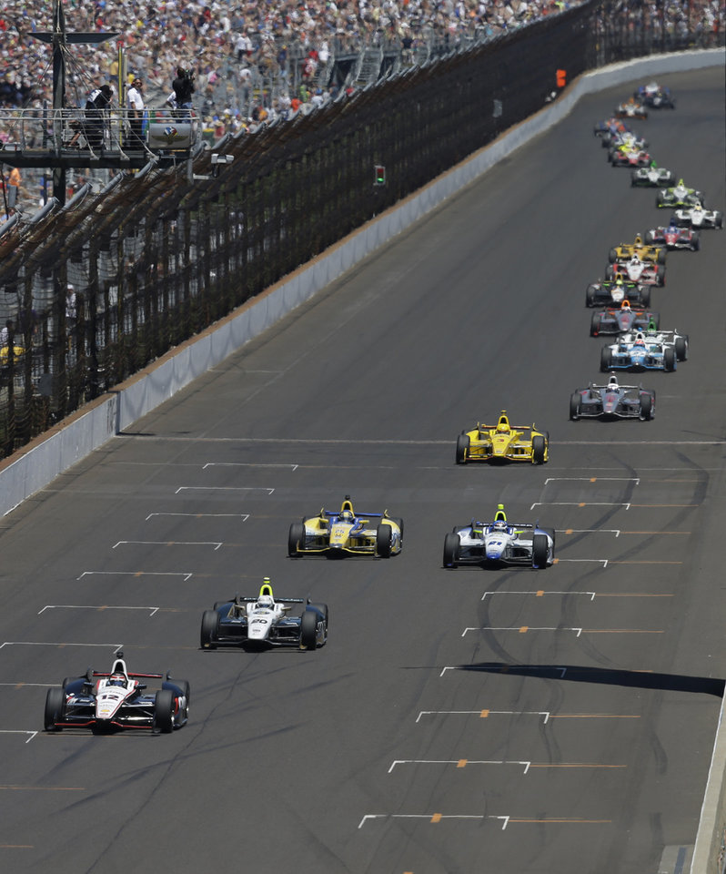 The field, lead by Will Power, of Australia, snakes down the main straightaway during the 98th running of the Indianapolis 500 IndyCar auto race at the Indianapolis Motor Speedway in Indianapolis, Sunday, May 25, 2014. (AP Photo/Darron Cummings)
