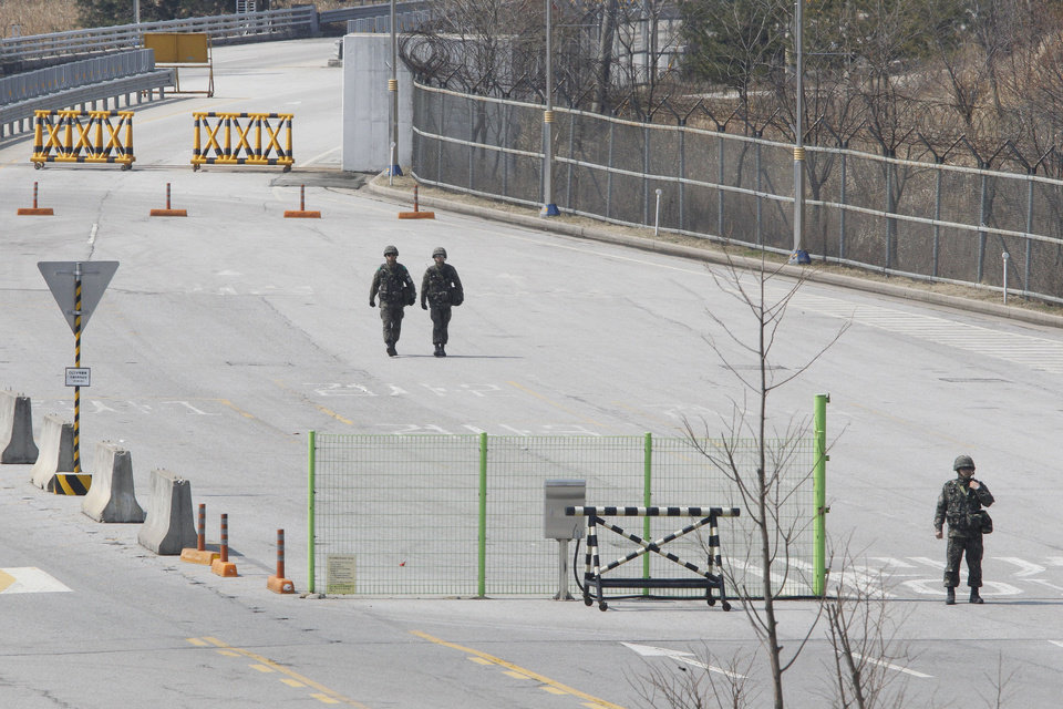 Photo - South Korean army soldiers walk on the empty road after South Korean vehicles which were refused for entry to North Korea at the customs, immigration and quarantine office in Paju, South Korea, near the border village of Panmunjom, Wednesday, April 3, 2013. North Korea on Wednesday barred South Korean workers from entering a jointly run factory park just over the heavily armed border in the North, officials in Seoul said, a day after Pyongyang announced it would restart its long-shuttered plutonium reactor and increase production of nuclear weapons material.(AP Photo/Ahn Young-joon)