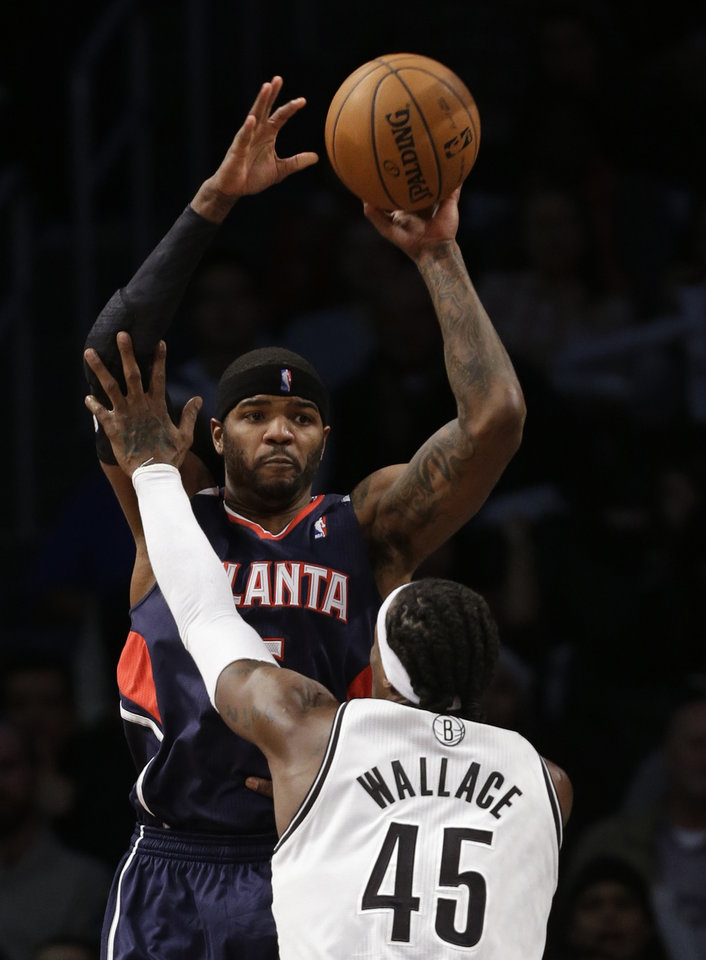 Atlanta Hawks forward Josh Smith, top, passes around the defense of Brooklyn Nets forward Gerald Wallace (45) in the first half of their NBA basketball game at the Barclays Center, Friday, Jan. 18, 2013, in New York. (AP Photo/Kathy Willens)