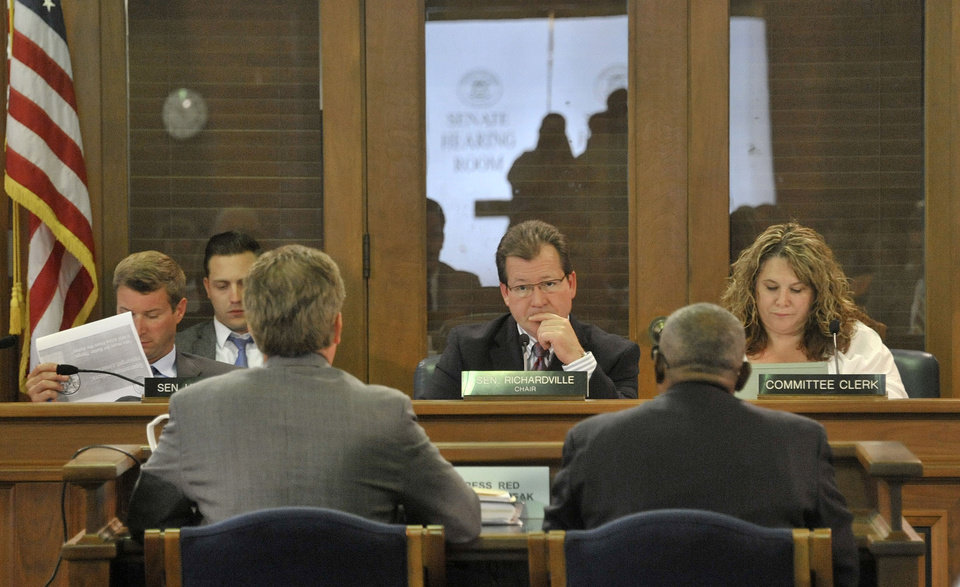 Photo - Under the leadership of Sen Randy Richardville, center, R-Monroe, the senate committee on Government Operations passed all the bills associated with easing Detroit's bankruptcy in Lansing, Mich., Tuesday, June 3, 2014. The Republican-led chamber voted 21-17 to contribute the state funds to join $466 million in commitments from 12 foundations and the Detroit Institute of Arts. The pool of money would shore up Detroit's two retirement systems while the city-owned art museum and its assets would be transferred to a private nonprofit. (AP Photo/Detroit News, Dale G. Young) DETROIT FREE PRESS OUT; HUFFINGTON POST OUT. MANDATORY CREDIT