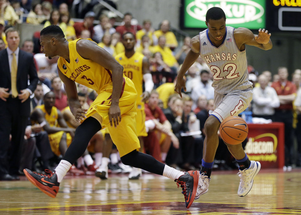 Photo - Kansas guard Andrew Wiggins, right, drives past Iowa State forward Melvin Ejim during the second half of an NCAA college basketball game, Monday, Jan. 13, 2014, in Ames, Iowa. Kansas won 77-70. (AP Photo/Charlie Neibergall)