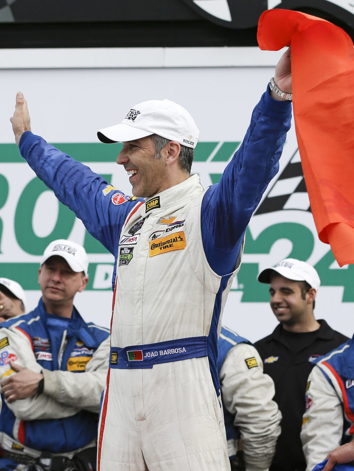 Photo - Joao Barbosa, of Portugal, celebrates in Victory Lane with the Action Express Corvette DP team after winning the IMSA Series Rolex 24 hour auto race at Daytona International Speedway in Daytona Beach, Fla., Sunday, Jan. 26, 2014.(AP Photo/John Raoux)