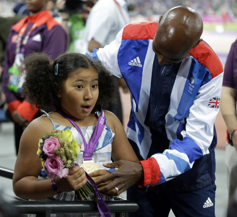 Photo -   Great Britain's Mohamed Farah shows off his gold medal to his stepdaughter Rihnna after the awards ceremony for the men's 5000-meter during the athletics in the Olympic Stadium at the 2012 Summer Olympics, London, Saturday, Aug. 11, 2012. (AP Photo/Matt Slocum)