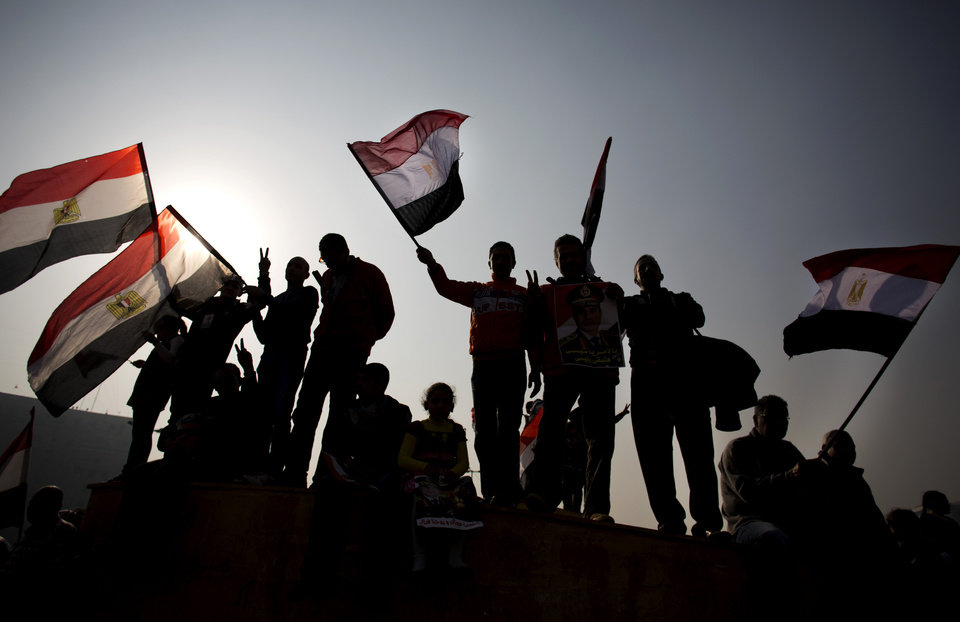 Photo - Egyptians hold national flags during a rally in Tahrir Square, in Cairo, Egypt, Saturday, Jan. 25, 2014. Egyptian riot police have fired tear gas to disperse hundreds of supporters of ousted Islamist President Mohammed Morsi protesting as the country marks the third anniversary of the 2011 uprising, as supporters of the military gathered in rival rallies in other parts of the capital, many of them urging military chief Gen. Abdel-Fattah el-Sissi, the man who removed Morsi, to run for president. (AP Photo/Khalil Hamra)