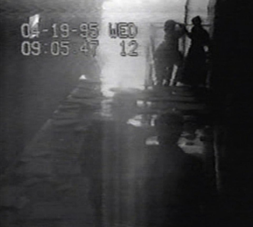 Photo - In this image from a security camera, a woman holds her head as she is helped out of a Southwestern Bell building in the minutes after the Oklahoma City bombing.
