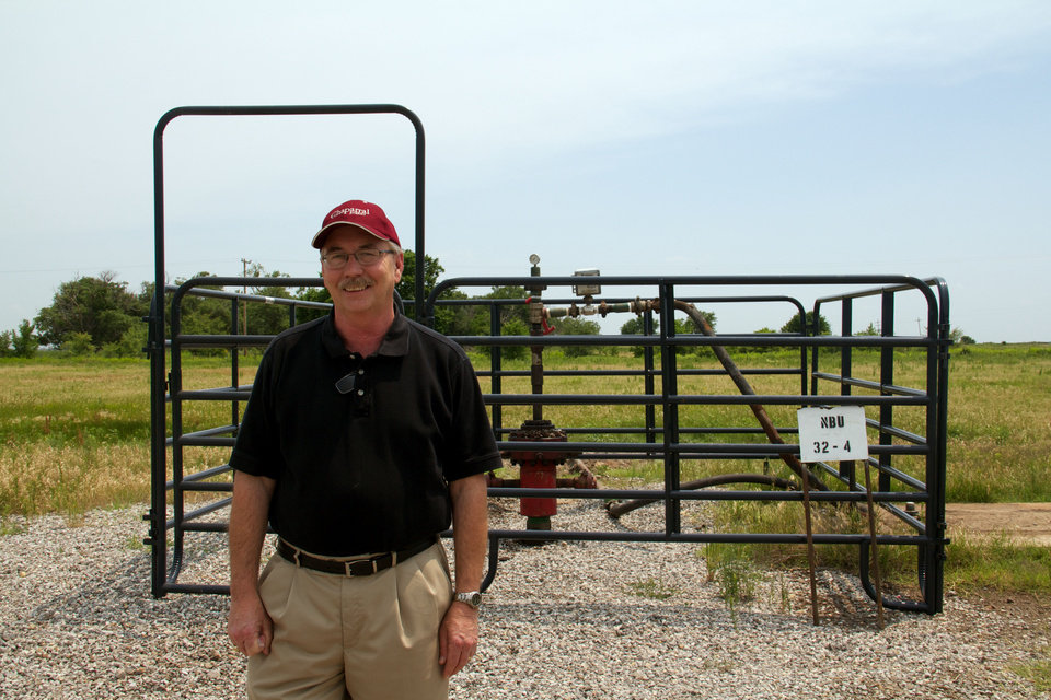Photo -  Larry Brinlee, Chaparral Energy's vice president of operations for the North Burbank field, stands in front of a production well in Osage County.  photo by Adam Wilmoth