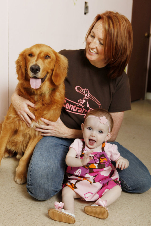 April Campbell, owner of Central Park Dog Daycare, with her 9-month-old daughter Callyn (CQ) and client Bailey, a golden retriever. <strong>PAUL B. SOUTHERLAND - THE OKLAHOMAN</strong>