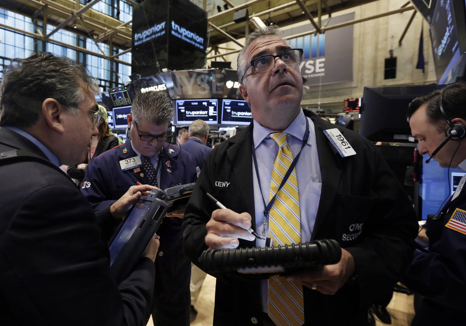 Photo - Kenneth Polcari, third left, works with fellow traders on the floor of the New York Stock Exchange Friday, July 18, 2014. U.S. stocks are opening higher after Google, Honeywell and other big companies report their quarterly results. (AP Photo/Richard Drew)