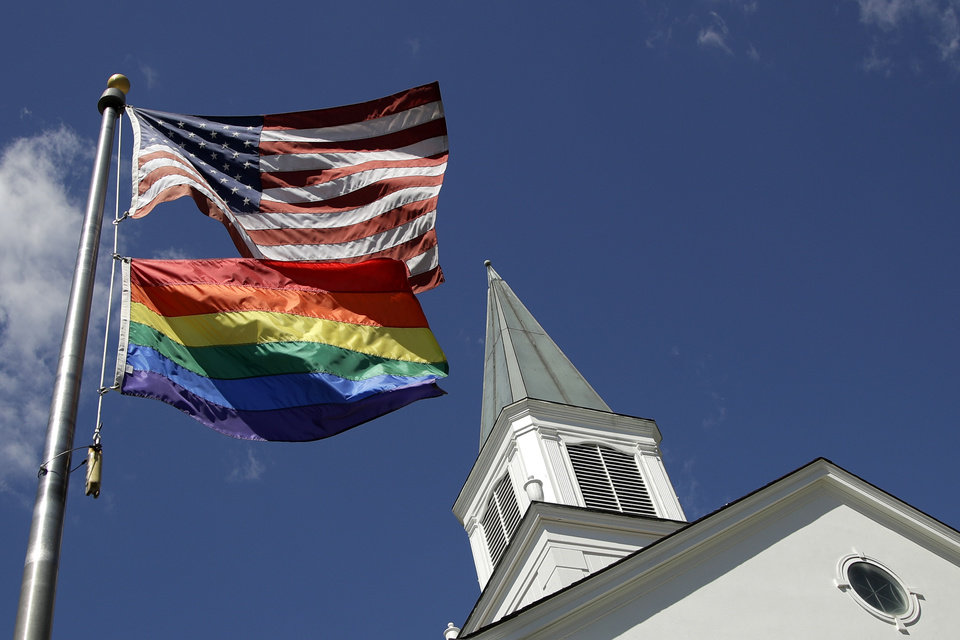 Photo - FILE - In this April 19, 2019, file photo, a gay pride rainbow flag flies along with the U.S. flag in front of the Asbury United Methodist Church in Prairie Village, Kan., United Methodist Church leaders are proposing creation of a separate division that would let more traditional denominations break away because of the disagreement with churches over the UMC's official stance on gay marriage. (AP Photo/Charlie Riedel, File)