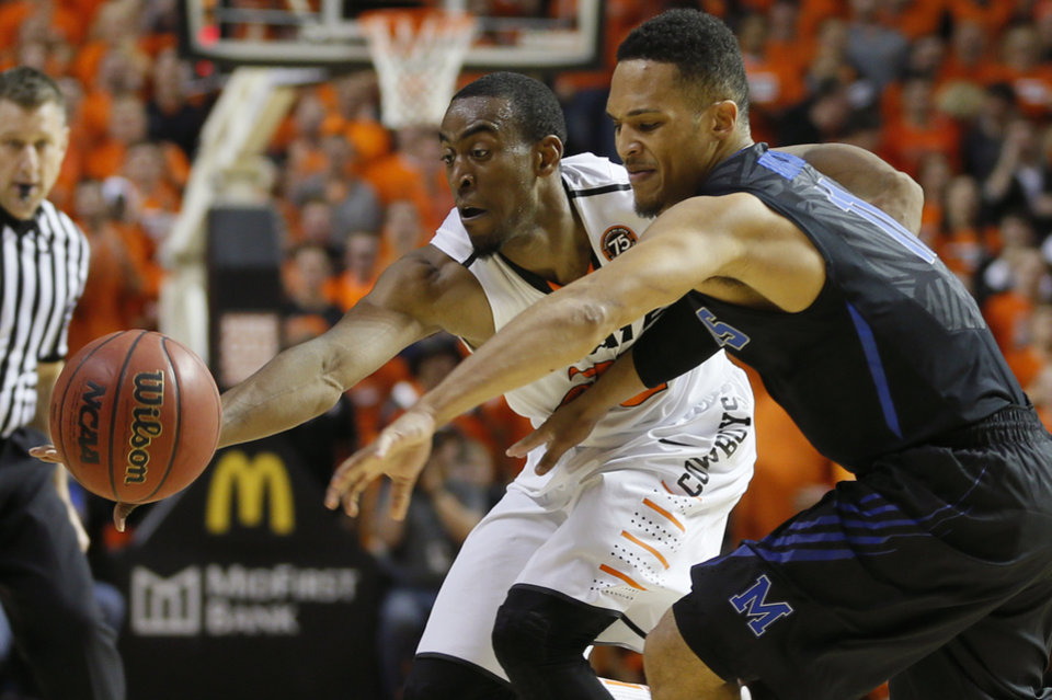 Photo - Oklahoma State's Markel Brown (22) reaches for the ball beside Memphis' Michael Dixon Jr. (11) during an NCAA college basketball game between Oklahoma State and Memphis at Gallagher-Iba Arena in Stillwater, Okla., Tuesday, Nov. 19, 2013. Photo by Bryan Terry, The Oklahoman