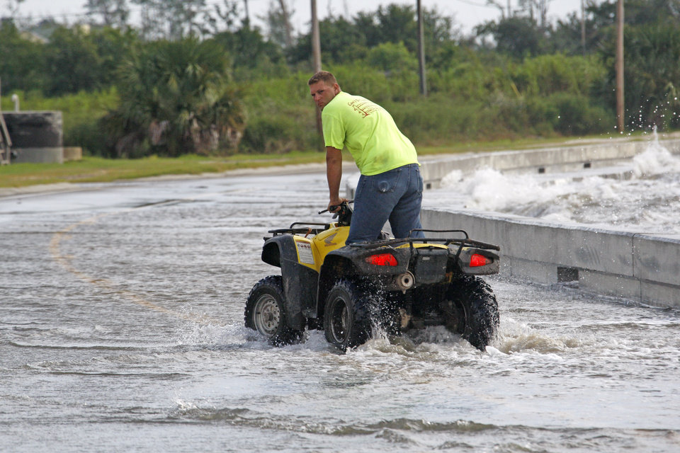 Brandon Ellis of Waveland takes advantage of the height of his ATV to ride up to the waves coming over the seawall alongside Beach Boulevard in Waveland, Miss., as Isaac\'s winds begin to hit the Mississippi Gulf Coast, Tuesday, Aug. 28, 2012. (AP Photo/Rogelio V. Solis)