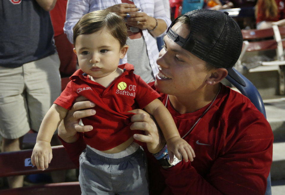 Photo - DJ Gasso cheers with his nephew Joesph Gasso, grandson of Patty Gasso, before the Women's College World Series softball game between OU and Washington at ASA Hall of Fame Stadium in Oklahoma City on  June 2, 2017. [Photo by Sarah Phipps/The Oklahoman]