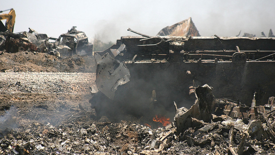 Photo - Train wreckage still smolders Monday near Goodwell. Two Union Pacific Railroad trains collided Sunday, killing two engineers and a conductor.  Photo by  Shawn Yorks,  The Guymon Daily Herald/AP