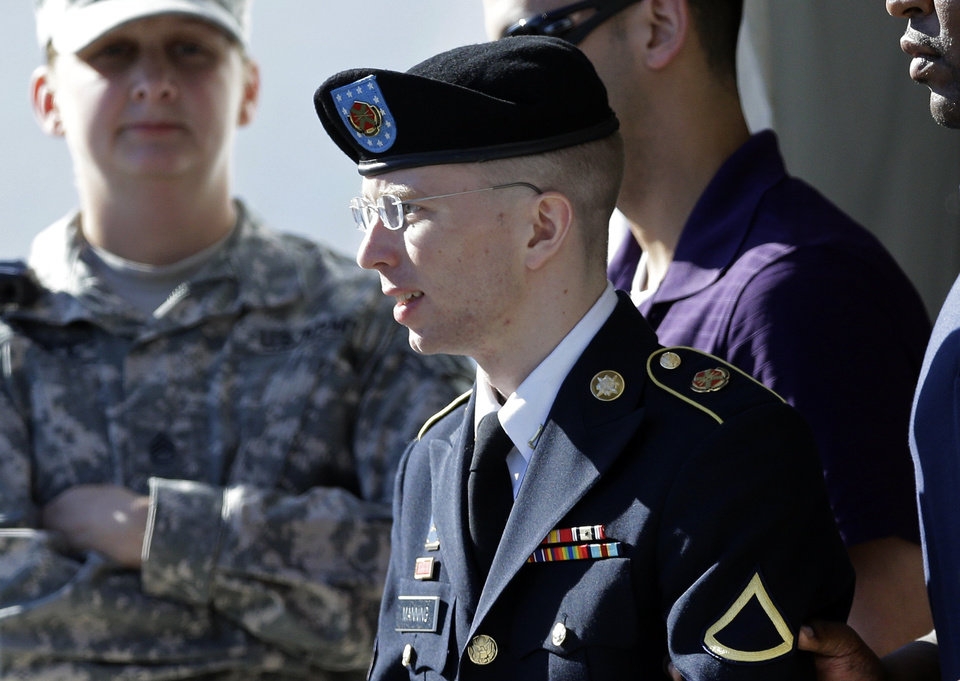 Army Pfc. Bradley Manning, front, is escorted out of a courthouse in Fort Meade, Md., Tuesday, June 4, 2013, after the second day of his court martial. Manning is charged with indirectly aiding the enemy by sending troves of classified material to WikiLeaks. He faces up to life in prison. (AP Photo/Patrick Semansky)