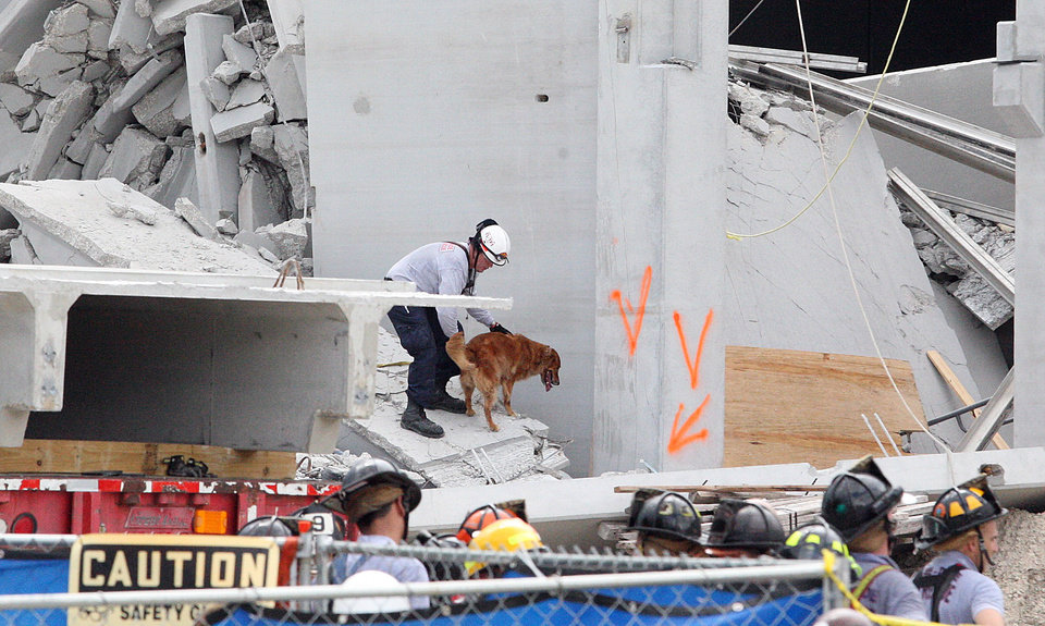 Photo -   Miami-Dade Fire Rescue workers work the scene of a parking garage collapse at Miami-Dade College in Doral, Fla. on Wednesday, Oct. 10, 2012. A section of the under-construction parking garage collapsed, killing one worker and trapping two others in the rubble, officials said. At least 10 other workers were hurt. (AP Photo/The Miami Herald, Hector Gabino) MAGS OUT