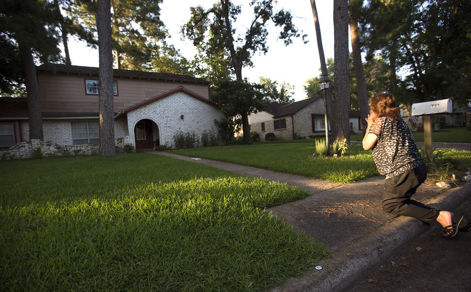 Photo - Patti Beller prays Thursday, July 10, 2014, in Spring, Texas, outside the home that was the scene of a multiple shooting the night before. The Harris County Sheriff's Office says Ronald Lee Haskell was booked Thursday on a capital murder/multiple murders charge and held without bond. Authorities believe Haskell fatally shot two adults and four children on Wednesday night and critically wounded a 15-year-old girl, who called 911. (AP Photo/Houston Chronicle, Cody Duty) MANDATORY CREDIT