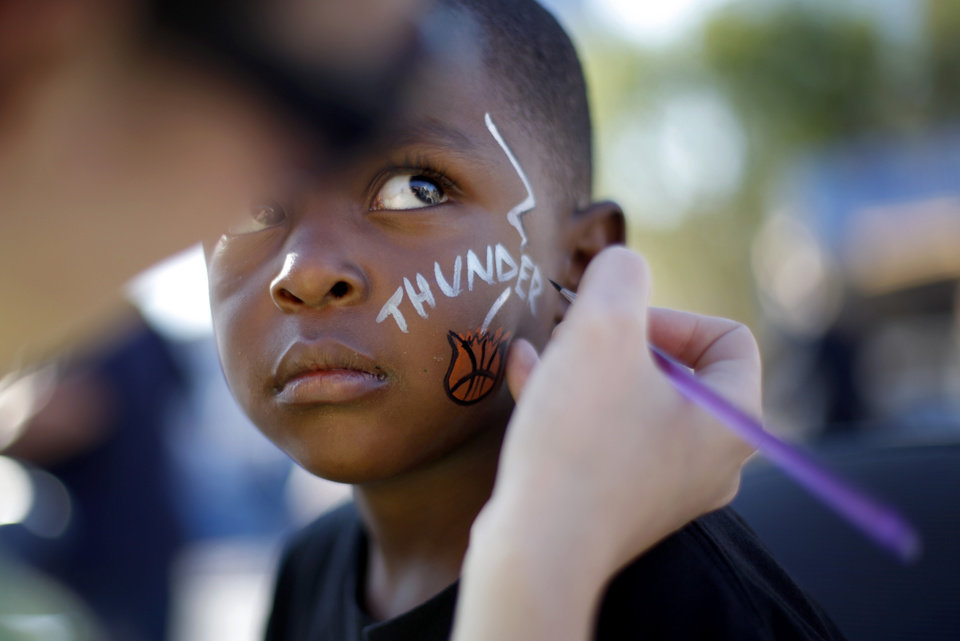 Photo - Jurney Ware, 3, of Oklahoma City gets his face painted before game two of the Western Conference semifinals between the Memphis Grizzlies and the Oklahoma City Thunder in the NBA basketball playoffs at Oklahoma City Arena in Oklahoma City, Tuesday, May 3, 2011. Photo by Bryan Terry, The Oklahoman