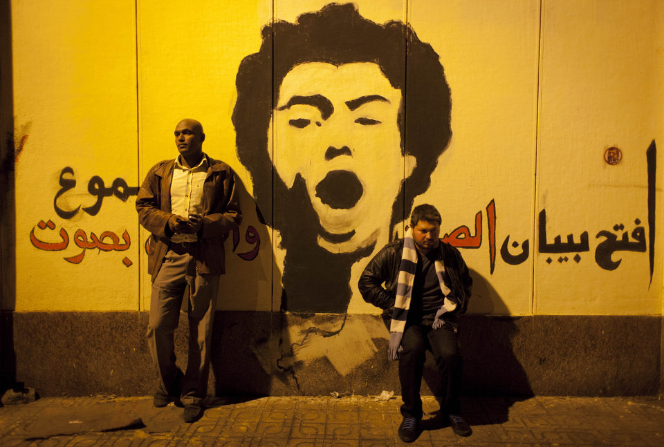 "Two Egyptian protesters takes a souvenir photo by graffiti that reads in Arabic ""open the doors of silence and shout loudly,"" made by the protesters at the walls of the presidential palace during protests opposing Muslim Brotherhood and Egyptian President Mohammed Mosri, after having broken through a barbed wire barricade keeping them from getting closer to the presidential palace, in Cairo, Egypt, Friday, Dec. 7, 2012. Egypt's political crisis spiraled deeper into bitterness and recrimination Friday as thousands of Islamist backers of the president vowed vengeance at a funeral for men killed in bloody clashes earlier this week and large crowds of the president's opponents marched on his palace to increase pressure after he rejected their demands. (AP Photo/Nasser Nasser)"