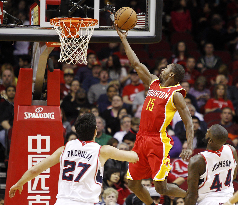Houston Rockets guard Toney Douglas (15) drives to the basket for a layup over Atlanta Hawks forward Ivan Johnson (44) and center Zaza Pachulia (27) during the first half of an NBA basketball game, Monday, Dec. 31, 2012, in Houston. (AP Photo/Bob Levey)