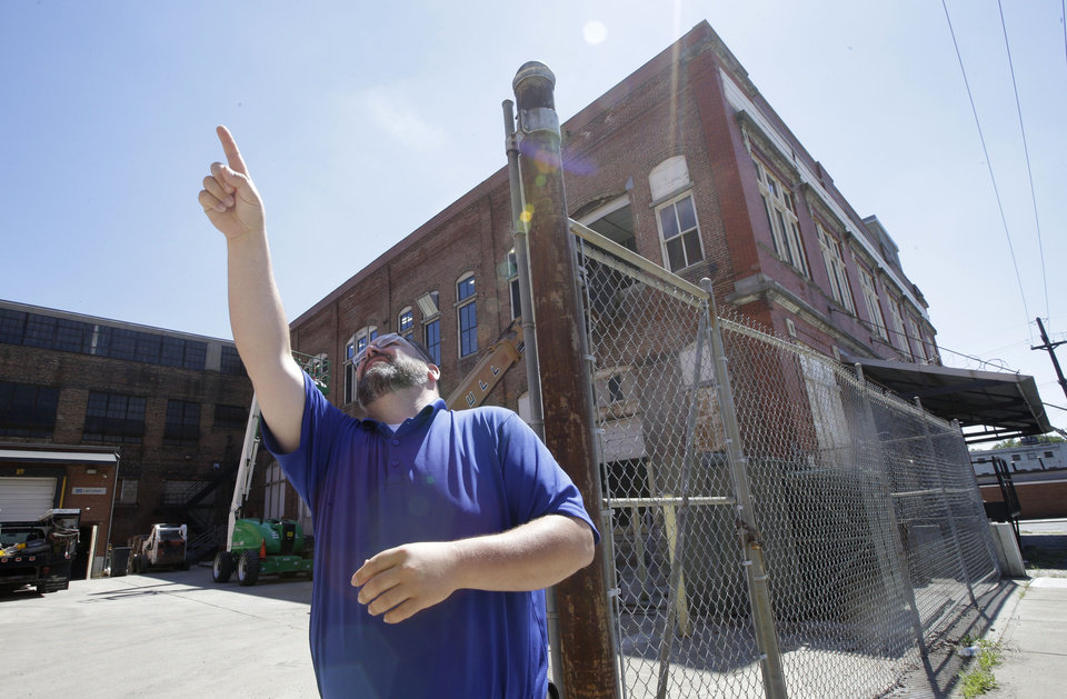 Photo - Steve Hampton, a local architect and the part-time executive director of the nonprofit Brewery District Community Urban Development Corp., points out locations of former breweries while standing outside a building that was part of the former Christian Moerlein complex, Wednesday, June 19, 2013, in Cincinnati. In the late 19th century, the district was at its peak, with 18 large breweries in operation. (AP Photo/Al Behrman)