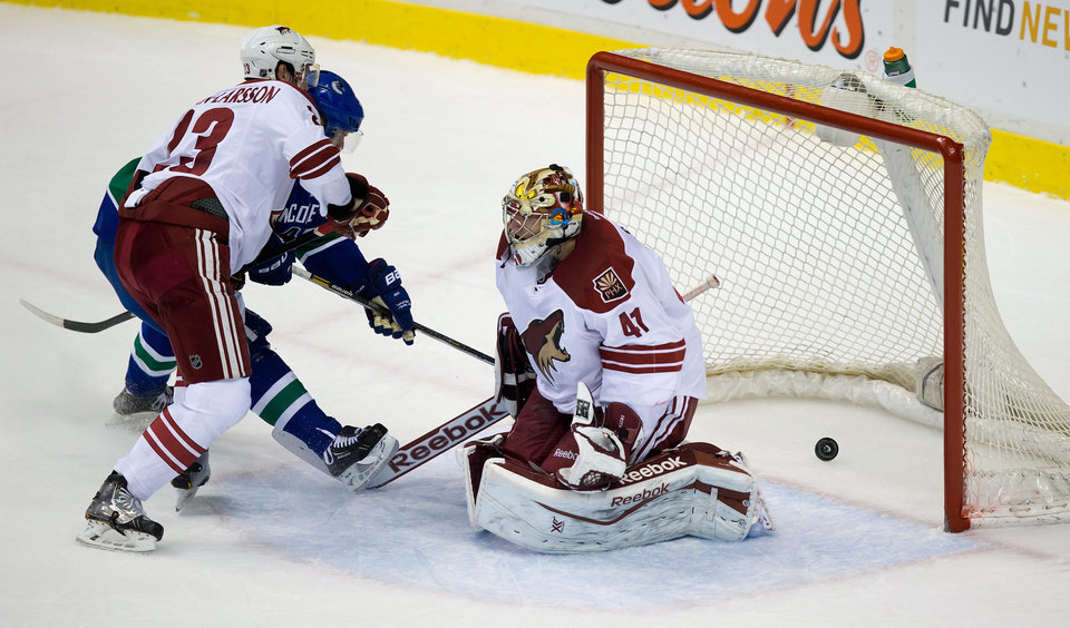 Photo - Phoenix Coyotes' Oliver Ekman-Larsson, left, of Sweden, checks Vancouver Canucks' Daniel Sedin, of Sweden, as Coyotes' goalie Mike Smith allows a goal to Canucks' Chris Higgins during the second period of an NHL hockey game in Vancouver, British Columbia, on Sunday, Jan. 26, 2014. (AP Photo/The Canadian Press, Darryl Dyck)