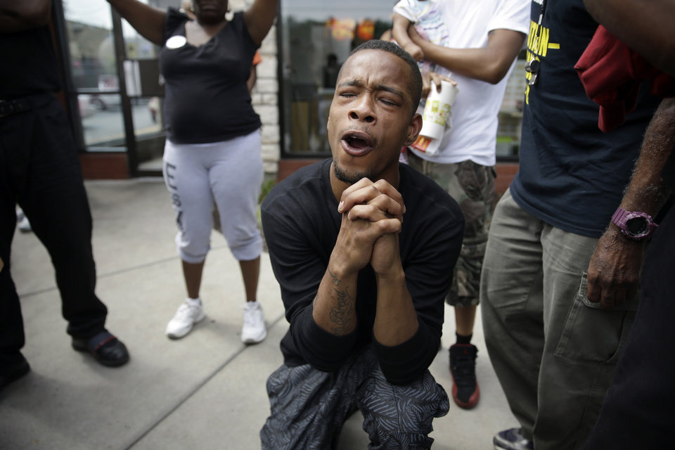 Photo - A man bends down in prayer as police try to disperse a small group of protesters Monday, Aug. 18, 2014, in Ferguson, Mo. The Aug. 9 shooting of Michael Brown by police has touched off rancorous protests in Ferguson, a St. Louis suburb where police have used riot gear and tear gas. Gov. Jay Nixon ordered the National Guard to help restore order Monday, while lifting a midnight-to-5 a.m. curfew that had been in place for two days. (AP Photo/Jeff Roberson)