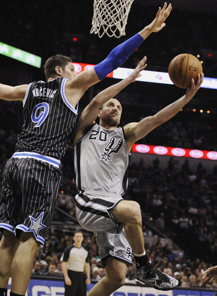 San Antonio Spurs guard Manu Ginobili, right, of Argentina, shoots against Orlando Magic center Nikola Vucevic during the first half of an NBA basketball game on Saturday, March 8, 2014, in San Antonio. (AP Photo/Darren Abate)