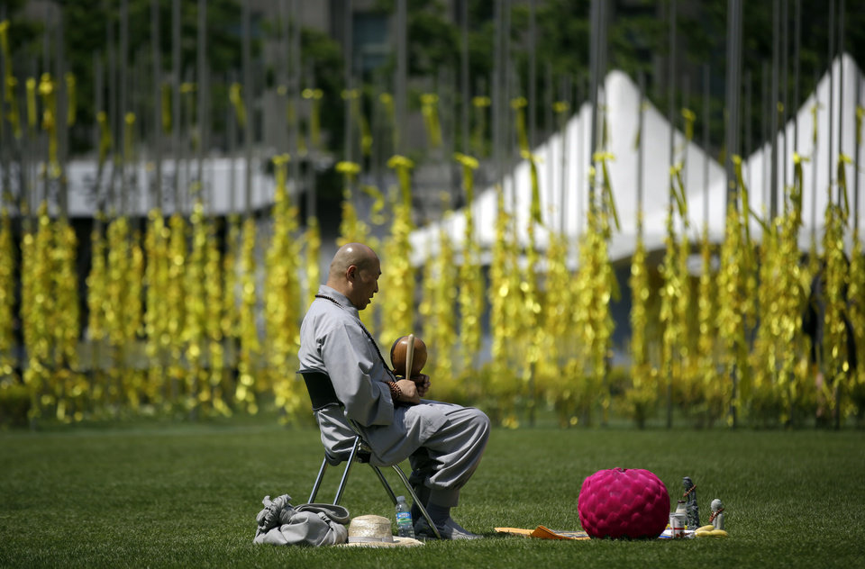 Photo - A Buddhist monk prays for the victims and missing passengers of the sunken ferry Sewol at a group memorial altar in Seoul, South Korea, Wednesday, May 7, 2014. The ferry disaster left more than 200 people dead, with others still missing. Government and civilian divers are fighting rapid currents as they try to retrieve the remaining bodies.(AP Photo/Lee Jin-man)