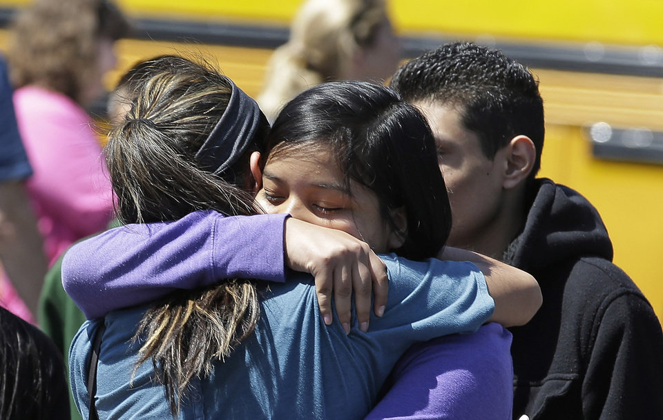 Photo - Sutdents embraces with family members after arriving at a shopping center parking lot in Wood Village, Ore., after a shooting at Reynolds High School Tuesday, June 10, 2014, in nearby Troutdale. A gunman killed a student at the high school east of Portland Tuesday and the shooter is also dead, police said. (AP Photo/Rick Bowmer)