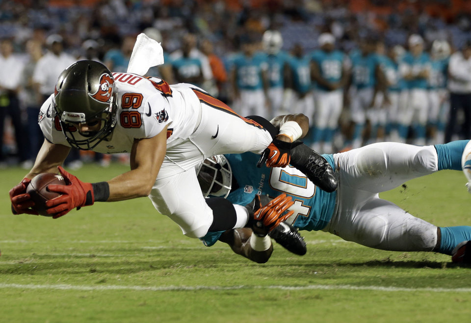 Photo - Tampa Bay Buccaneers wide receiver David Douglas (89) stretches for a touchdown as Miami Dolphins defensive back Keelan Johnson (40) holds his legs during the second half of an NFL preseason football game on Saturday, Aug. 24, 2013, in Miami Gardens, Fla. The Buccaneers defeated the Dolphins 17-16. (AP Photo/Lynne Sladky)