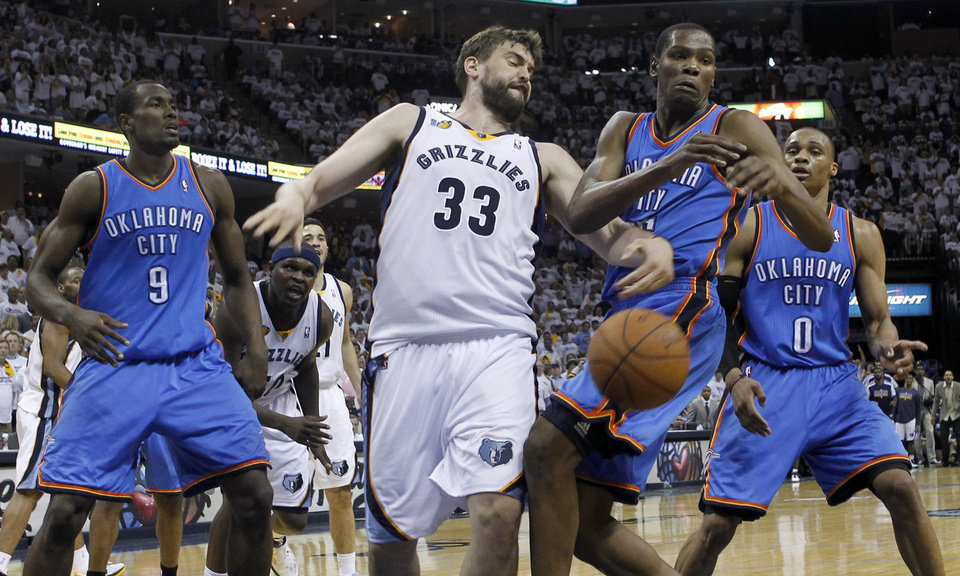 Photo - Memphis Grizzlies center Marc Gasol (33), of Spain, knocks the ball away from Oklahoma City Thunder forward Kevin Durant during the third overtime of Game 4 of a second-round NBA basketball playoff series on Tuesday, May 10, 2011, in Memphis, Tenn. Oklahoma City won 133-123 in triple overtime. Also shown are Oklahoma City Thunder forward Serge Ibaka (9) and Russell Westbrook (0). (AP Photo/Lance Murphey)