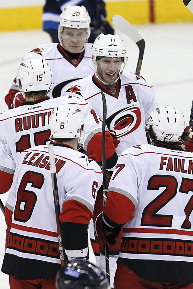 Photo - Carolina Hurricanes' Jordan Staal (11), Alexander Semin (28), Tuomo Ruutu (15), Tim Gleason (6) and Justin Falk (27) celebrate Ruutu's goal against the Winnipeg Jets during the second period of their NHL hockey game in Winnipeg, Manitoba, Thursday, April 18, 2013. (AP Photo/The Canadian Press, John Woods)