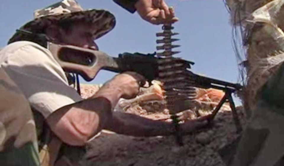 Photo - In this Tuesday, June 17, 2014 image taken from video obtained from British Broadcaster Sky, which has been authenticated based on its contents and other AP reporting, a Kurdish solider fires his weapon towards positions held by fighters of the Islamic State of Iraq and the Levant near Jalula, Iraq. Kurdish security forces are engaged in gun battles with Sunni militants in the northern Iraqi town of Jalula, according to British Broadcaster Sky. Footage showed Kurdish fighters known as peshmerga using heavy artillery and rockets to attack militant positions on Tuesday. (AP Photo/Sky via AP video)