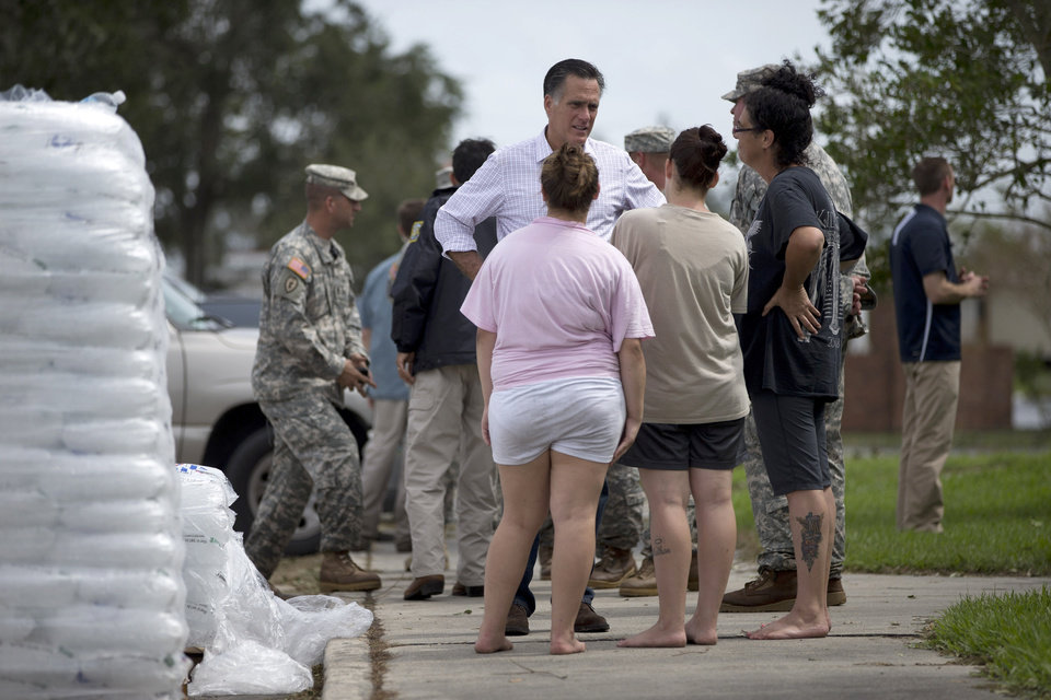 Photo -   Republican presidential candidate, former Massachusetts Gov. Mitt Romney talks with local residents during a tour of areas flooded hurricane Isaac, Friday, Aug. 31, 2012, in Jean Lafitte, La. (AP Photo/Evan Vucci)