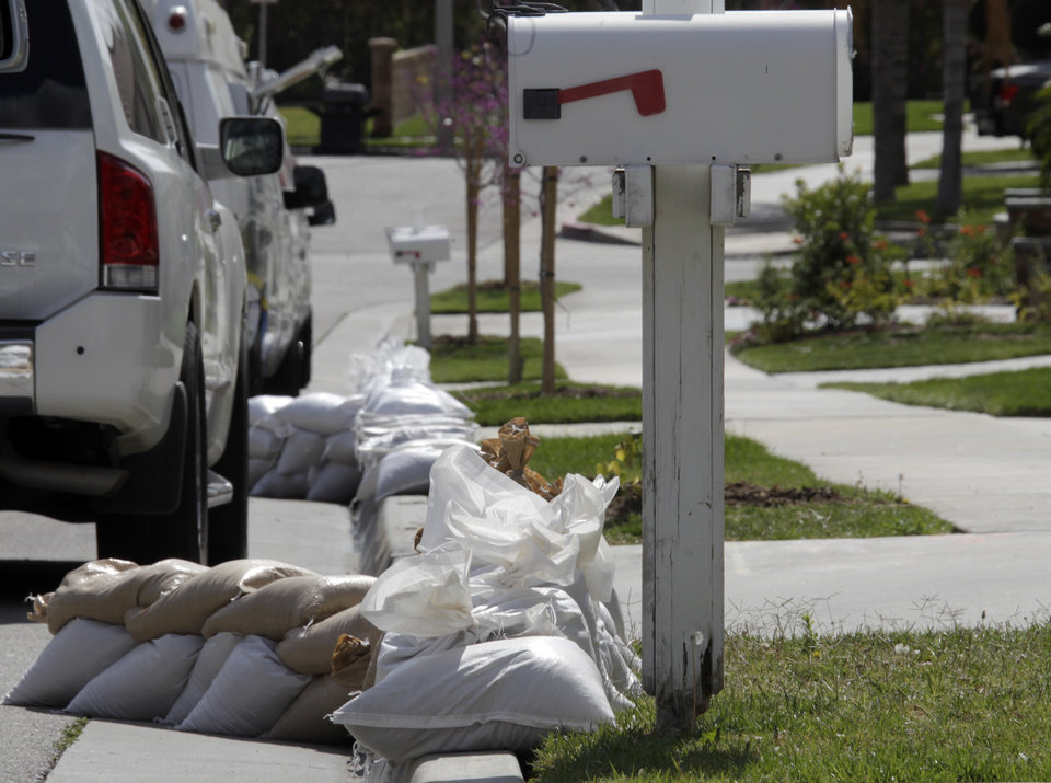 Photo - Sandbags line a street considered especially at risk in Azusa, Calif., as the city makes preparations for possible flooding Thursday, Feb. 27, 2014. In advance of a powerful Pacific storm, mandatory evacuation orders have been issued for 1,000 homes in Glendora and Azusa, two of Los Angeles' eastern foothill suburbs, which are located beneath nearly 2,000 acres of steep mountain slopes left bare by a January fire. (AP Photo/Reed Saxon)