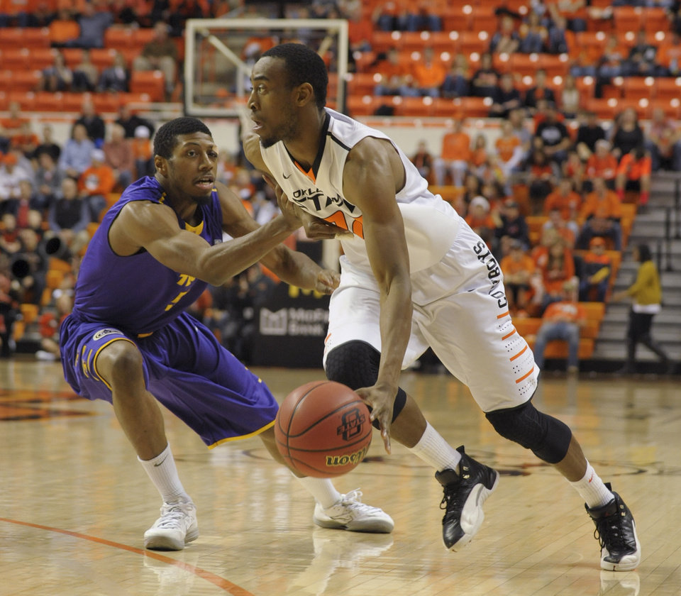 Oklahoma State guard, Markel Brown, right, drives past Tennessee Tech guard, Javon McKay, left, during the first half of an NCAA college basketball game, Saturday, Dec. 22, 2012, in Stillwater, Okla. (AP Photo/Brody Schmidt)