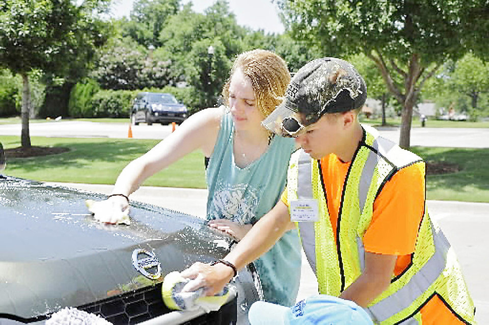 Chantel Beaudoin and Hunter Hill scrub down a car during a fundraising car wash at All Souls' Episcopal Church sponsored by Bishop McGuinness High School students to help a teacher who lost his home in the Moore tornado. Photo by M. Tim Blake, for The Oklahoman <strong>M. Tim Blake - for The Oklahoman</strong>