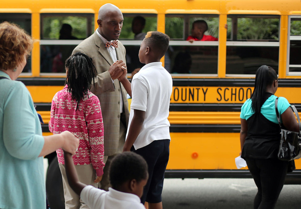 Photo - Ronald E. McNair Discovery Learning Academy assistant principal Johnny Potter, center, greets a student Wednesday, Aug. 21, 2013, a day after an armed suspect caused an ordeal at their school in Decatur, Ga. The learning academy held classes at McNair High School on Wednesday after a gunman on Tuesday held one or two staff members captive and fired into the floor of the school office. As officers swarmed the campus outside, he shot at them at least a half a dozen times with an assault rifle from inside the school and they returned fire, police said. (AP Photo/Atlanta Journal-Constitution, Jason Getz)