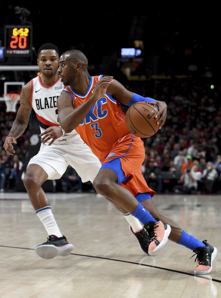 Photo - Oklahoma City Thunder guard Chris Paul, right, drives to the basket past Portland Trail Blazers guard Kent Bazemore, left, during the first half of an NBA basketball game in Portland, Ore., Sunday, Dec. 8, 2019. (AP Photo/Steve Dykes)