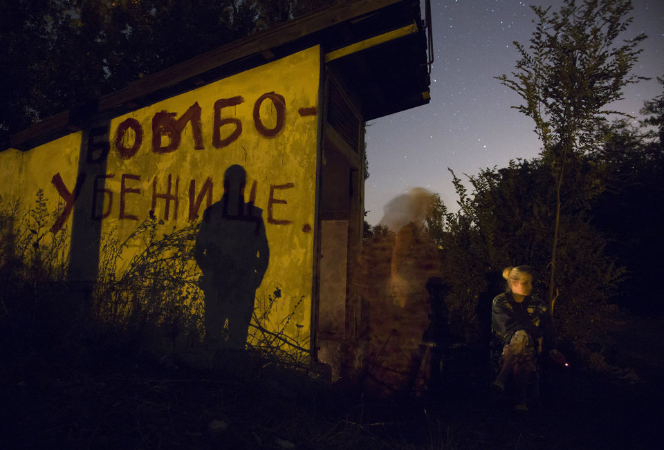 Photo - Local residents sit near an entrance to a bomb shelter as they exit to get some fresh air during a short cease fire in Petrovsky district in the city of Donetsk, eastern Ukraine Tuesday, Aug. 5, 2014. (AP Photo/Dmitry Lovetsky)