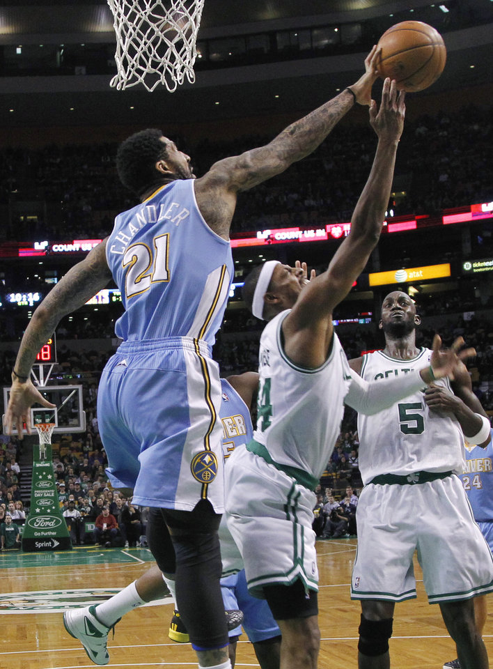 Denver Nuggets guard Wilson Chandler (21) blocks a shot-attempt by Boston Celtics forward Paul Pierce (34) as forward Kevin Garnett (5) looks on during the first half of an NBA basketball game in Boston, Sunday, Feb. 10, 2013. (AP Photo/Elise Amendola)