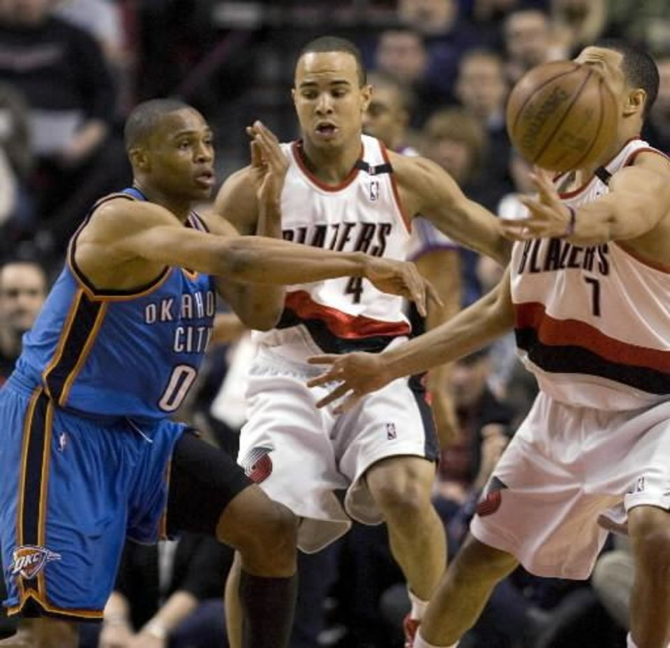 Photo - Oklahoma City Thunder guard Russell Westbrook, left, passes off against Portland Trail Blazers' Brandon Roy, right, and  Jerryd  Bayless during the first half of their NBA basketball game in Portland, Ore., Wednesday, Feb. 11, 2009.(AP Photo/Don Ryan)