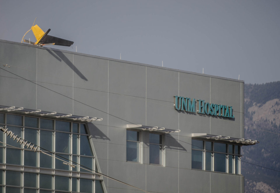 Photo - A helicopter's tail hangs over the edge of the UNM Hospital  Wednesday afternoon, April 9, 2014, when it crashed as it took off from the roof of the building.    (AP Photo/The Albuquerque Journal, Roberto E. Rosales)  THE SANTA FE NEW MEXICAN OUT