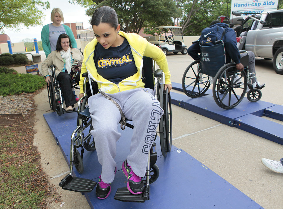 Photo - University of Central Oklahoma freshman Kayla Rogers navigates a wheelchair through an obstacle course as part of disability awareness week on the Edmond campus. PHOTOS BY DAVID MCDANIEL, THE OKLAHOMAN